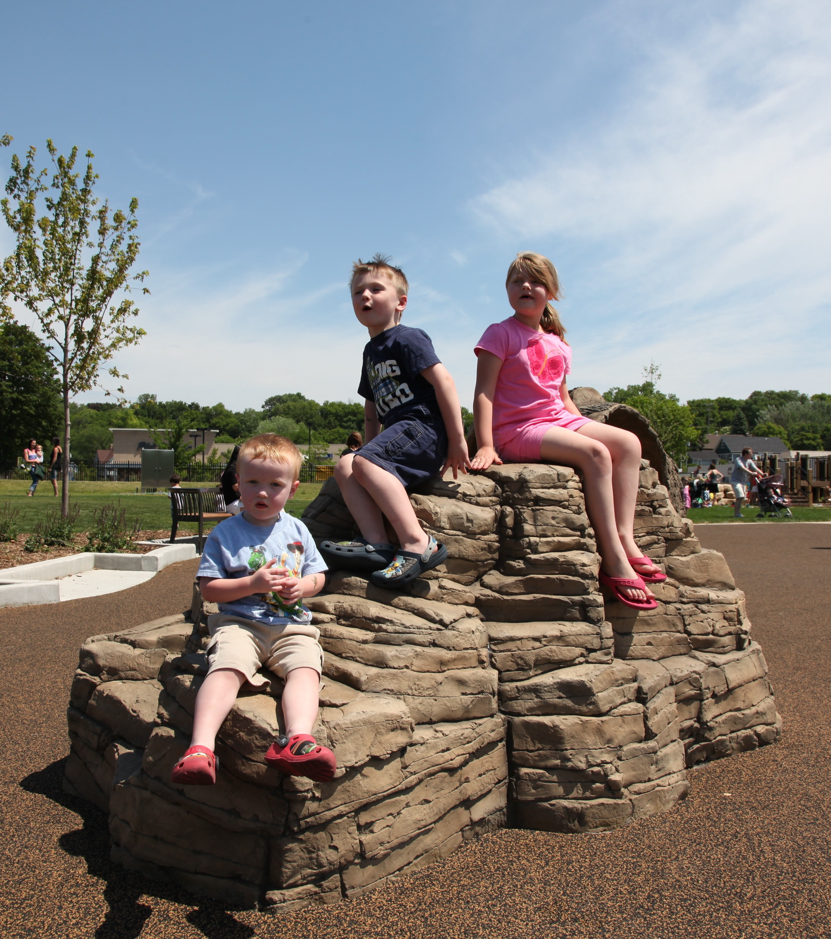 Kids sit on a rock in a nature-themed playground in Hart Park, Wauwatosa, WI.